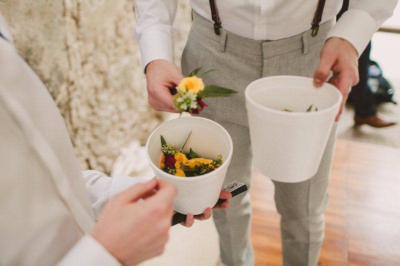 Groom making his boutonniere before his destination wedding