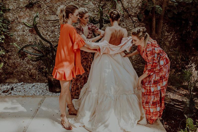 bridemaids help dress bride