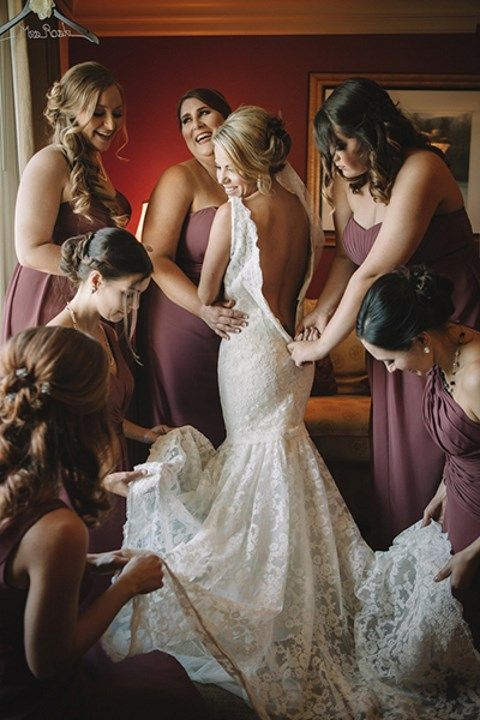 bridemaids helping bride in the getting ready